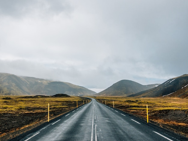 Strada circondata da colline ricoperte di vegetazione e neve sotto un cielo nuvoloso in islanda Foto Gratuite