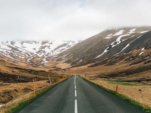 Strada circondata da colline ricoperte di neve e nebbia nel verde in islanda Foto Gratuite