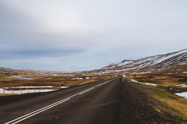 Strada circondata da colline coperte di neve e vegetazione sotto un cielo nuvoloso in islanda Foto Gratuite