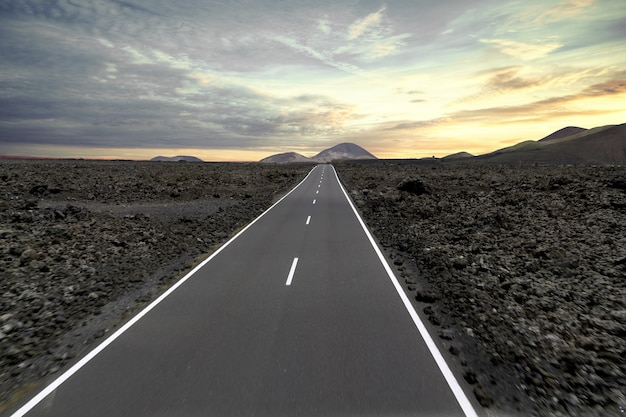 Road surrounded by hills and stones during the sunset in the timanfaya national park in spain Free Photo