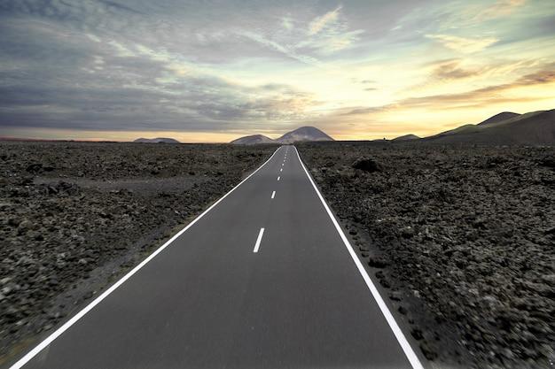 Strada circondata da colline e pietre durante il tramonto nel parco nazionale di timanfaya in spagna Foto Gratuite