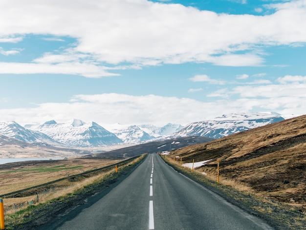 雪に覆われたロッキー山脈の丘に囲まれた道路 無料写真