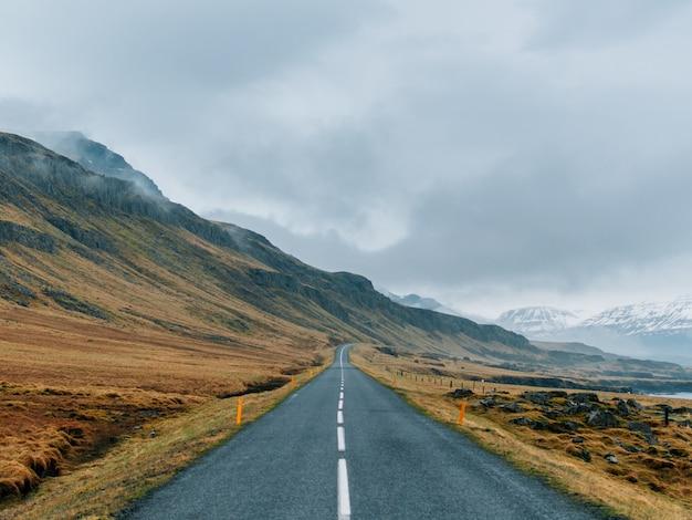 曇り空と霧の下で緑と雪に覆われた岩に囲まれた道路 無料写真