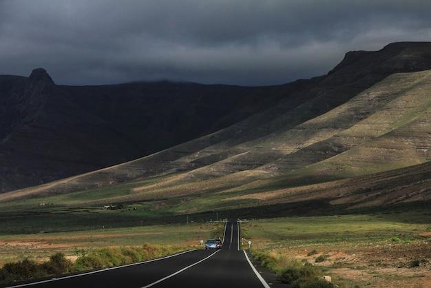 Дорога с вождения автомобилей на расстоянии в середине травянистых полей и гор в фоновом режиме Бесплатные Фотографии