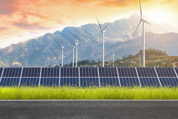 Road with solar panels with wind turbines against mountanis landscape against sunset sky Premium Photo