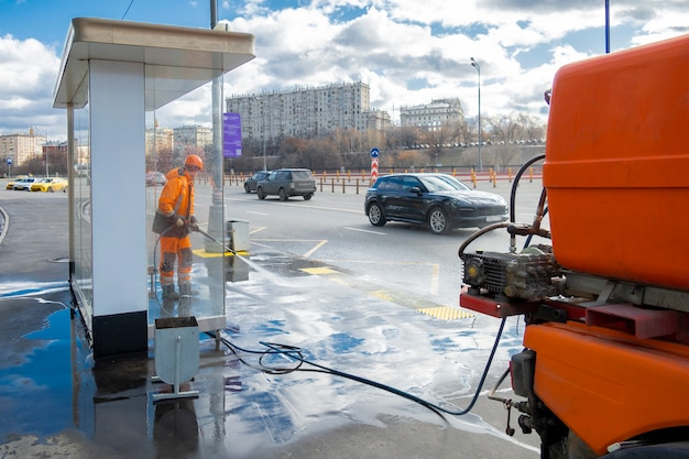 Road worker cleaning city street with high pressure power washer, moscow, russia Premium Photo