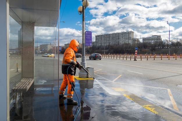 Road worker cleaning dirty public transport stops, moscow, russia Premium Photo