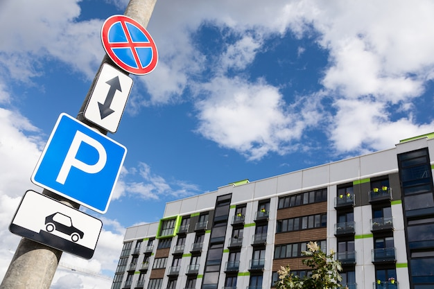 Roadsigns no waiting and method of parking vehicle against sky and apartment building Premium Photo