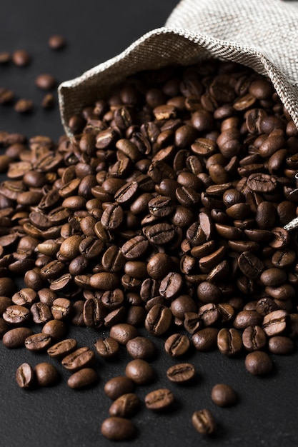 Roasted beans of tasteful coffee spilled from sack Free Photo