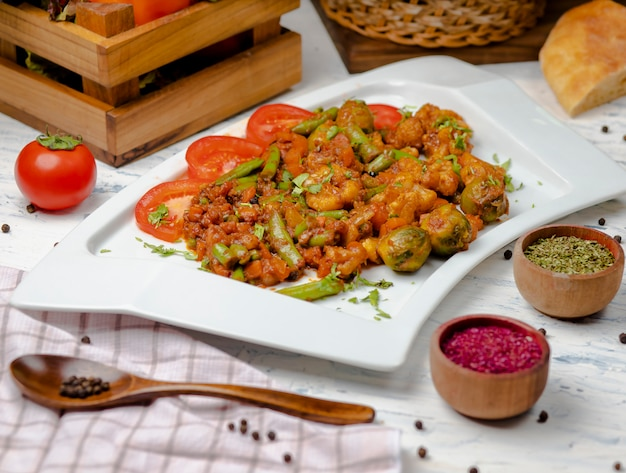 Roasted cauliflower with sprouts, beans and served with tomato sauce and herbs. Free Photo