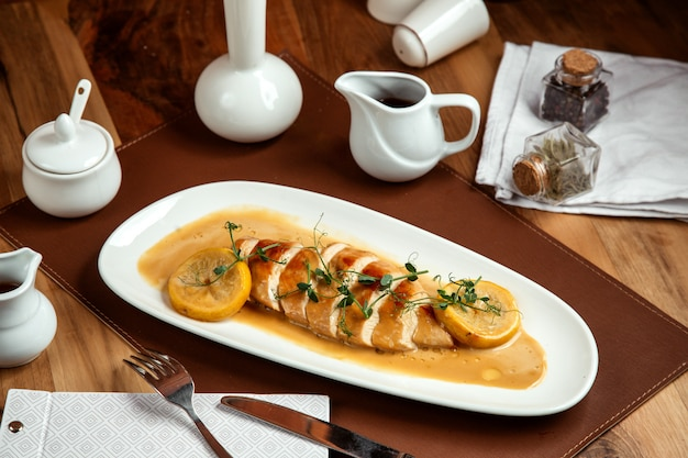 Roasted chicken breast with creamy sauce and lemon on plate Free Photo
