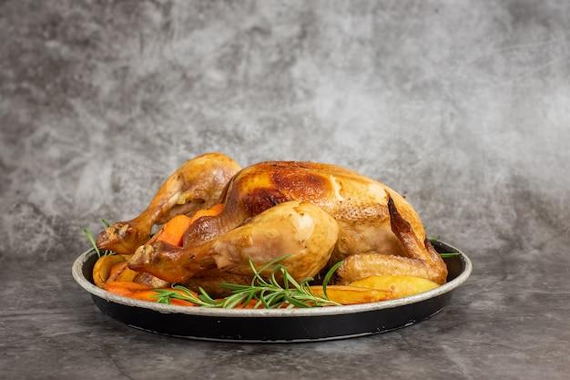 회색 접시에 구운 닭고기, 감자, 야채. 측면보기. 프리미엄 사진
