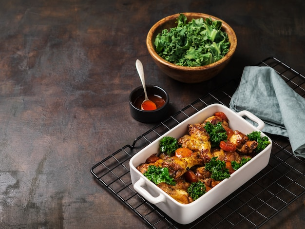 Roasted chicken wings with carrots, kale, garlic and dipping sauce. Premium Photo