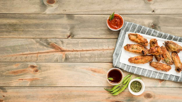 Roasted chicken wings with various savoury sauces Free Photo