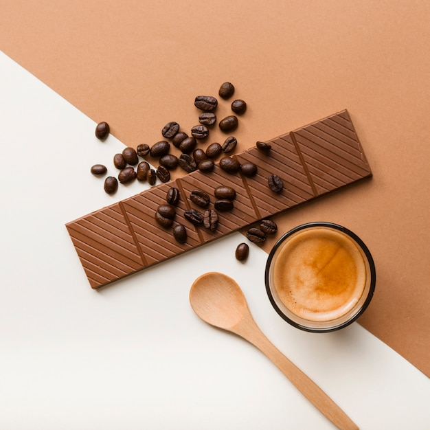 Roasted coffee beans; coffee cup and chocolate bar on dual backdrop Free Photo