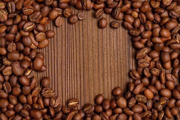 Жареные кофейные зерна создают круг для копирования пространство на фоне сожгли деревянный фон. Premium Фотографии