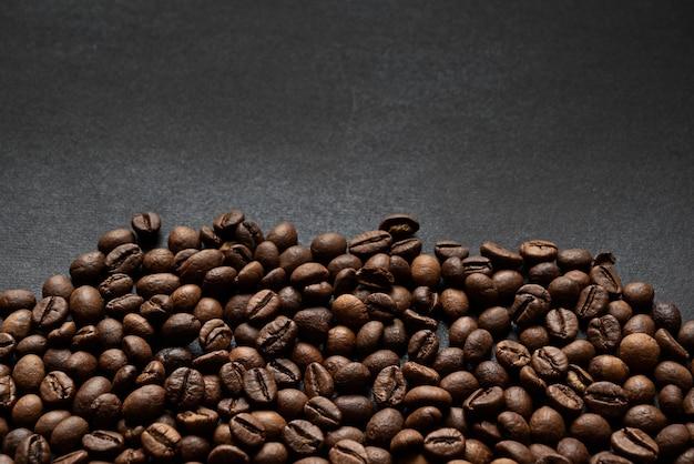 暗い表面に散らばった焙煎コーヒー豆 Premium写真