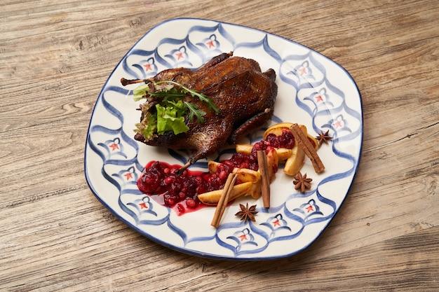 마 르 멜로 나무 테이블 배경에 구운 된 오리입니다. 모과와 베리 소스로 구운 오리 전체. 프리미엄 사진