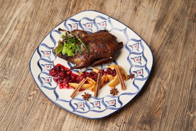 木製のテーブルの背景にマルメロと鴨のロースト。アヒル全体をマルメロとベリーソースで焼き上げました。 Premium写真