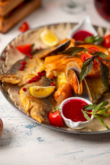 Roasted grilled fish and seafood served with herbs, lemon and dip red tomato sauce. Free Photo