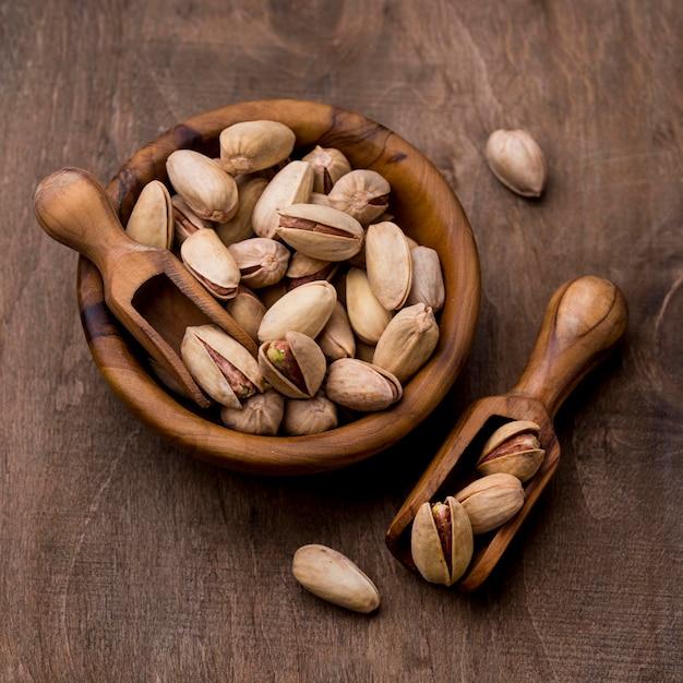木製ボウルでローストしたピスタチオナッツ 無料写真