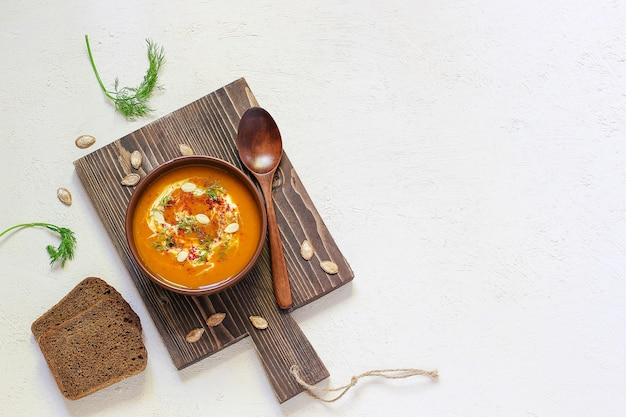 Roasted pumpkin and carrot soup with cream, black pepper and pumpkin seeds , cutting board and fresh pumpkin slices, black bread Free Photo