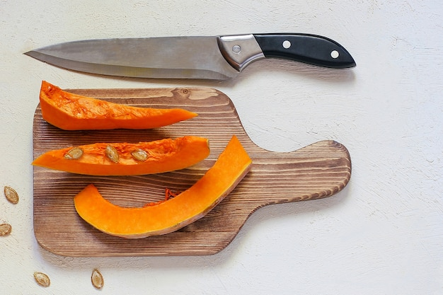 Roasted pumpkin and carrot soup with cream, black pepper and pumpkin seeds, cutting board and fresh pumpkin slices, black bread Free Photo