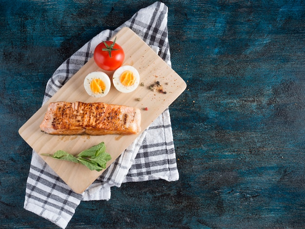 Roasted salmon with boiled egg on board Free Photo