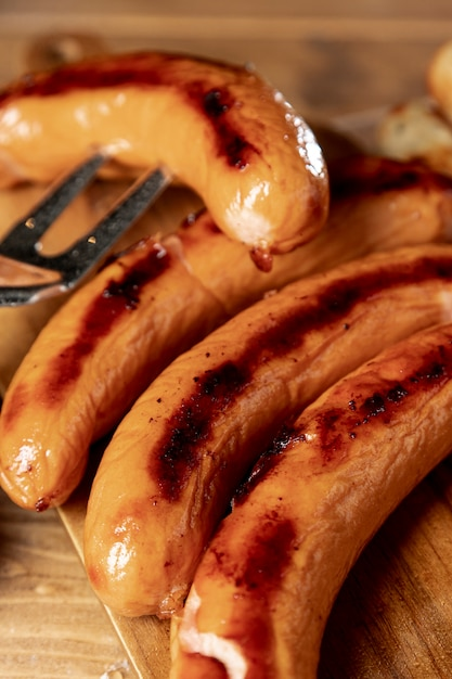 Roasted sausages with grill fork on a table Free Photo