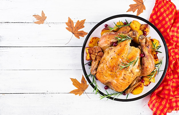 Roasted turkey garnished with cranberries on a rustic style table decorated  autumn leaf. thanksgiving day. baked chicken. top view Premium Photo