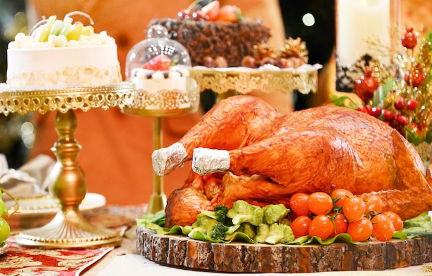 Roasted turkey.table served with turkey in christmas dinner, decorated with candles. Premium Photo