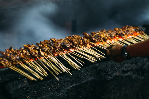Roasting meat, chicken and mutton satays with charcoal, fire and smoke. Premium Photo