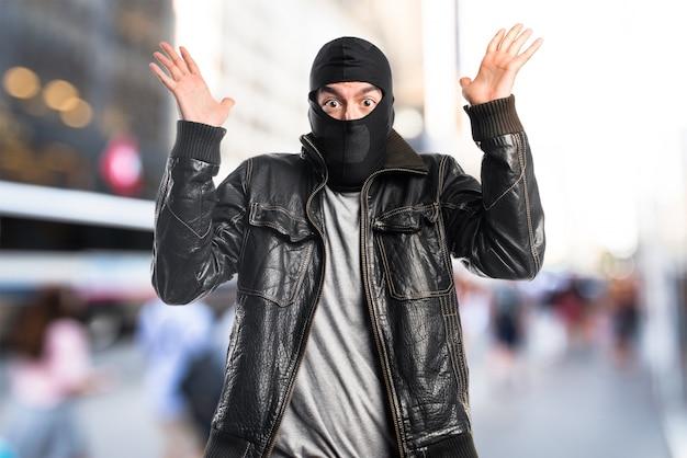 Разбойник делает неожиданный жест на несфокусированном фоне Premium Фотографии