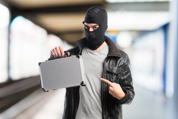 Robber holding a briefcase Free Photo