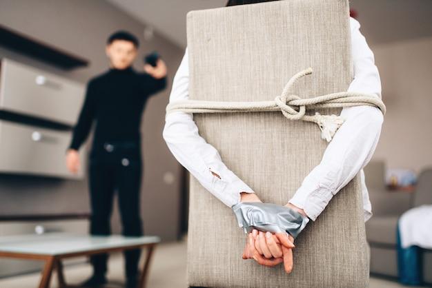 검은 옷을 입은 강도는 희생자가 의자에 밧줄과 테이프로 묶인 것을 두려워합니다. 집에서 강도, 미치광이 아파트에 침투 프리미엄 사진