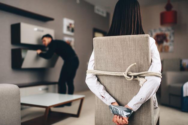 의자에 밧줄과 테이프로 묶인 여성 피해자를 상대로 집의 캐비닛을 수색하는 검은 옷을 입은 강도. 집에서 강도, 미치광이가 아파트에 침투했습니다. 실내의 위험한 갱스터 프리미엄 사진