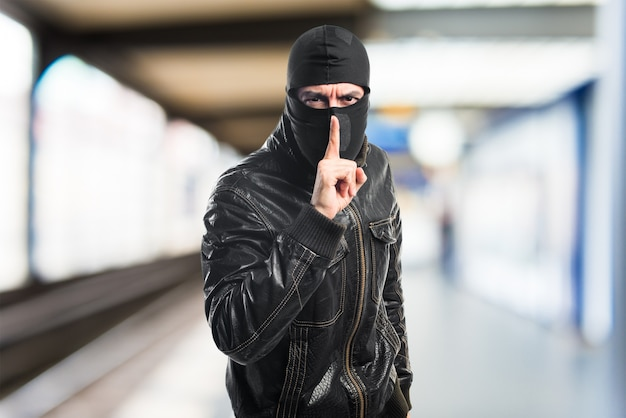 Robber making silence gesture Free Photo