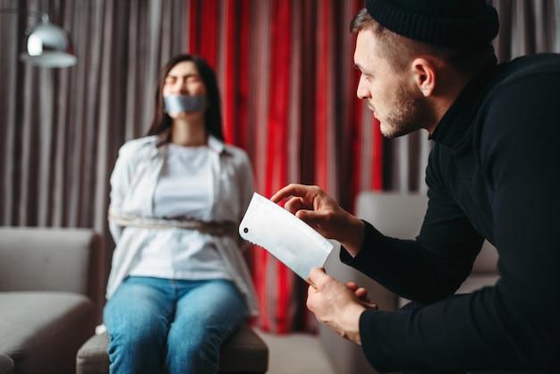 검은 옷을 입은 강도 광이 의자에 밧줄과 테이프로 묶인 여성 희생자에게 날카로운 칼을 보여줍니다. 집에서 강도, 갱스터가 아파트에 침투 프리미엄 사진
