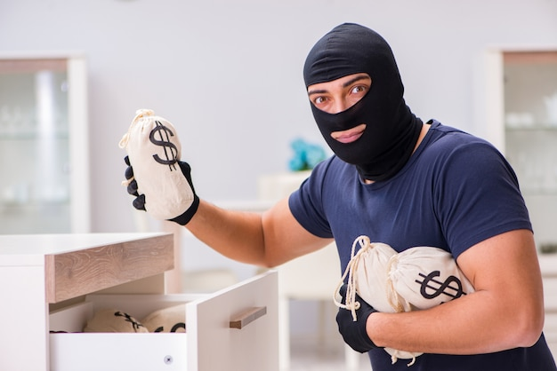 Robber wearing balaclava stealing valuable things Premium Photo
