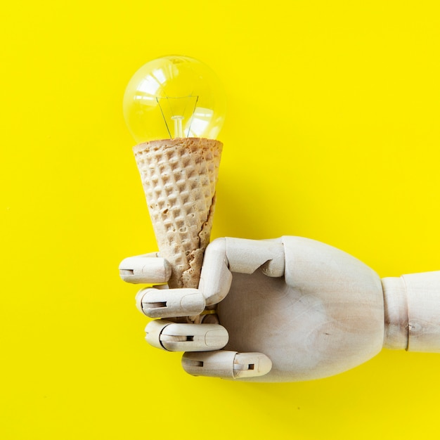 Robot hand holding a light bulb ice cream Free Photo