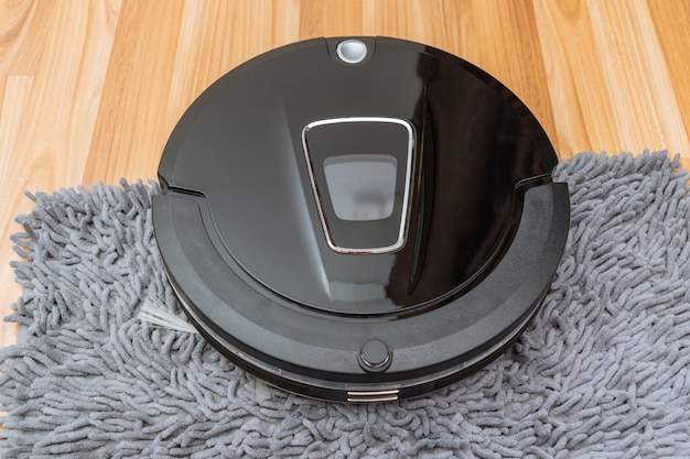 Robotic vacuum cleaner on laminate wood floor smart cleaning technology at home Premium Photo