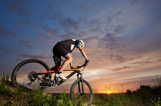 Robust and sporty man sitting on bicycle and cycling. energetic cyclist riding bike on trail with grass Premium Photo
