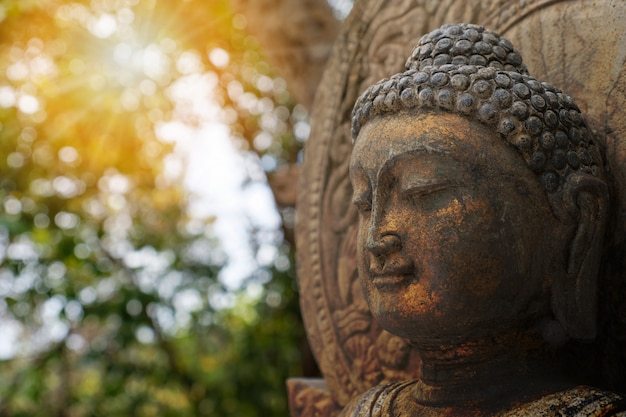 Rock buddha statue with sunlight used for amulets of buddhism religion. Premium Photo