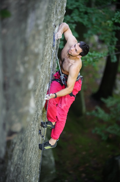 Rock climber climbs on large boulders with rope engaged Premium Photo