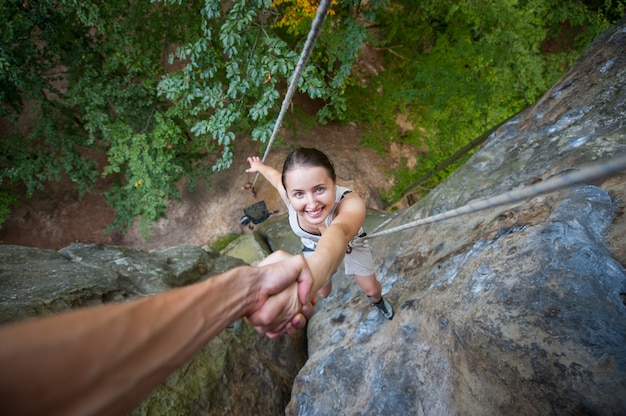 Rock climber is holding a sporty female climber by hand on a rocky wall Premium Photo