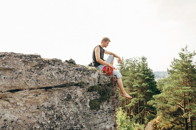 Rock climber sitting at the edge of the cliff with a rope Premium Photo