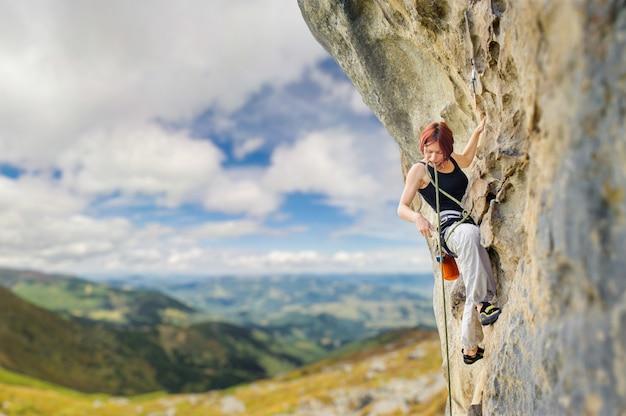 Rock climber on steep overhanging rock cliff Premium Photo
