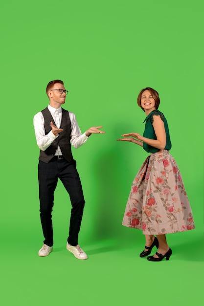 ロックンロール。緑のスタジオの背景に分離して踊る昔ながらのファッションの若い女性。若いスタイリッシュな男性と女性。 無料写真