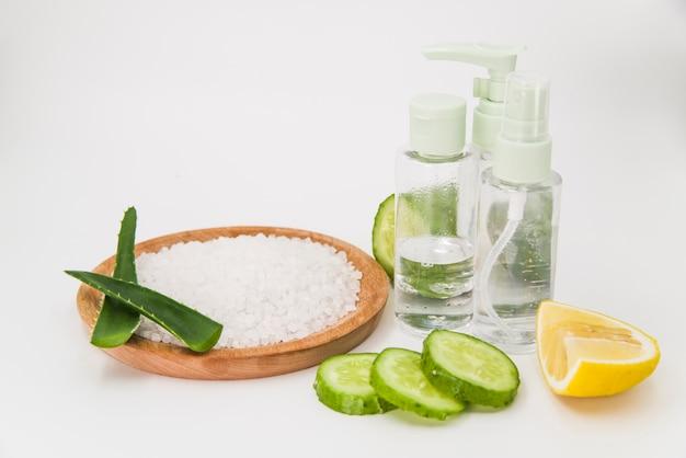 Rock salt on wooden plate; cucumber slices; lemon and spray bottle on white backdrop Free Photo