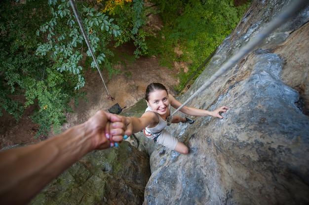 Rockclimber helping to female climber to reach top of mountain Premium Photo